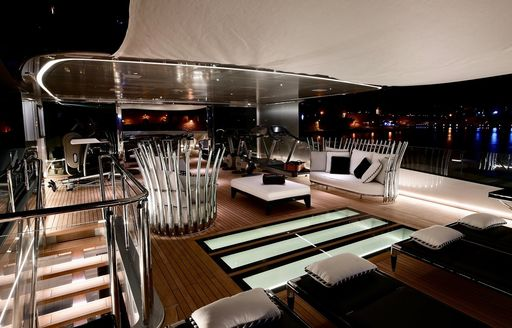 A collection of sleek furnishings and gymnasium equipment on the sundeck of a superyacht at night