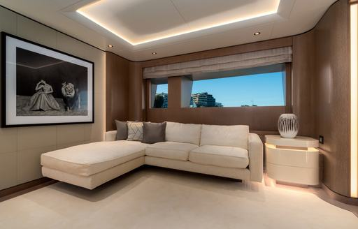 Comfortable seating on superyacht O'PARI with large photo on the wall and windows behind