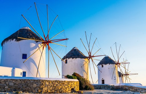 Three windmills line up in the countryside on Mykonos, Greece