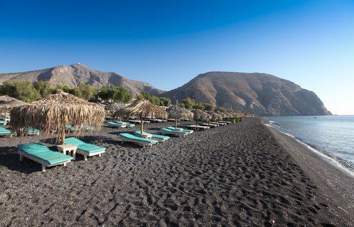 sun beds line up on the black sand beach of Kamari in Santorini
