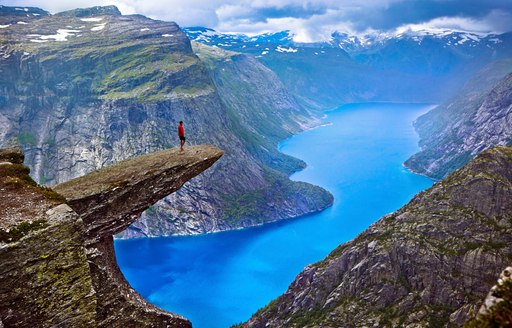Hiker stands on the edge of Hiker on Trolltunga Rock looking out across the Norwegian Fjords