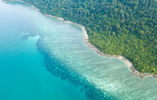 Aerial view of Beautiful coral reef along the tropical island coast with emerald clear water, part of Great Barrier Reef