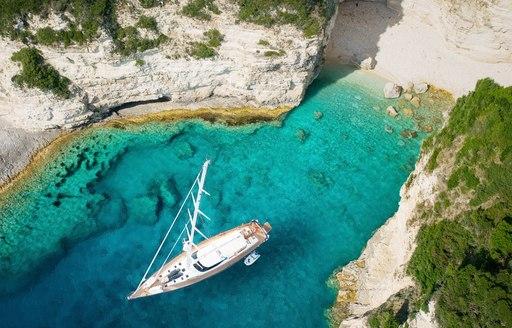 A sailing yacht anchored in a Mediterranean cove