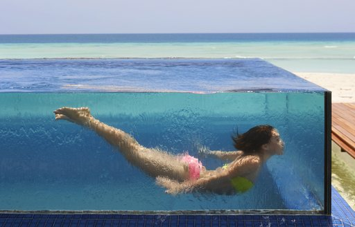 glass-rimmed infinity pool on thanda island with indian ocean in background