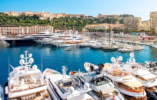 Motor yachts moored in Monaco marina, with hotels and facilities around dockside.