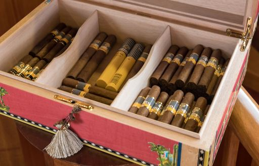 detail shot of box of vintage cigars on board luxury charter yacht over the rainbow's main salon