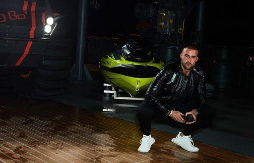Philipp Plein crouching in front of tender on Explorer yacht RAGNAR