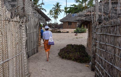woman walks though fishing village on remote island in tanzania