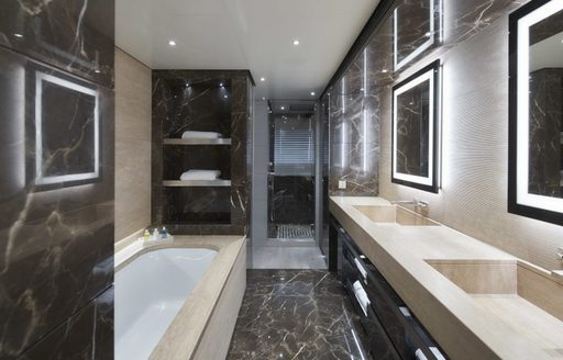 Looking into marble en-suite bathroom on superyacht SEVERIN'S with bath to the left and sinks to the right