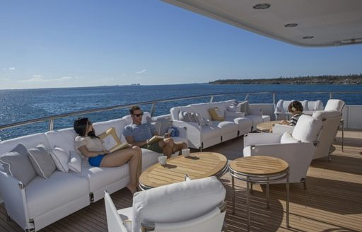 Guests relaxing on outside deck of explorer yacht MARCATO with sea in background
