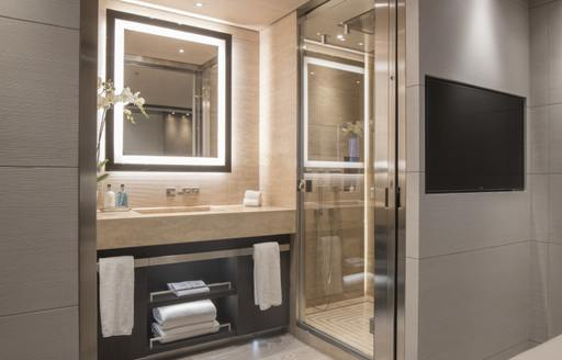 En-suite bathroom on superyacht SEVERIN'S with square mirror and shower cubicle to the right