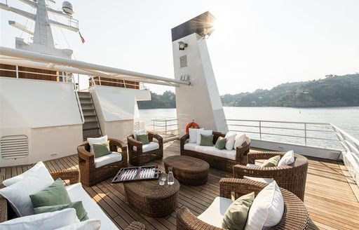 Tables and chairs on sundeck of superyacht 'Bleu De Nimes' with coast in background