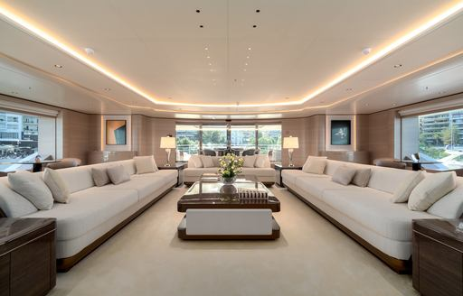 Open plan living room on superyacht O'PARI, with lightly colored sofas and table in center of room with windows all around