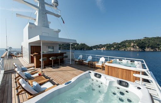 Sundeck on superyacht 'Bleu De Nimes' with double Jacuzzi, sunloungers and coast in background