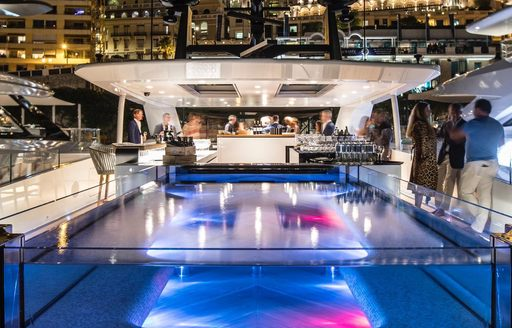 Pool on superyacht SEVERIN'S at night with guests standing talking