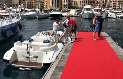Women and men leaving a tender to step onto a red carpet port