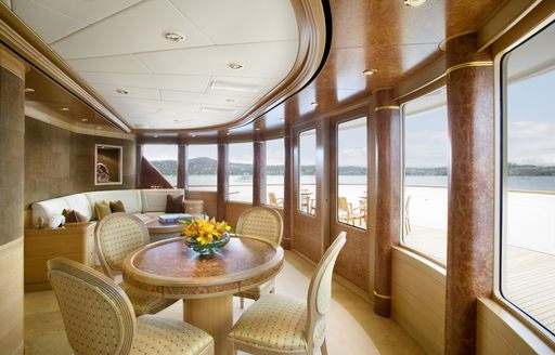 Traditionally styled chairs surround a table situated in the interior of a superyacht