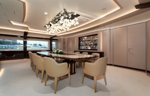 Dining table and chairs on superyacht O'PARI with intricate lighting above