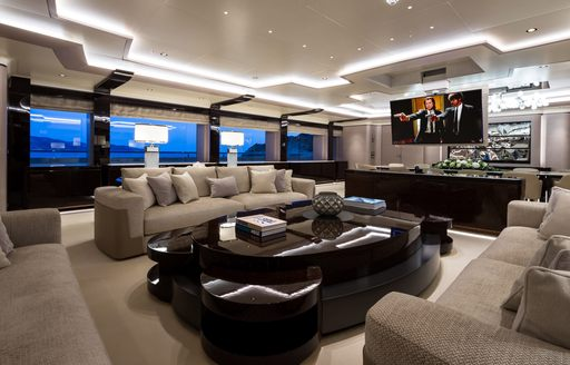 Elegant table and chairs on superyacht O'PARI with TV screen in background