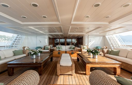 Undercover seating area on superyacht 'Bleu De Nimes', with cream sofas and wooden tables