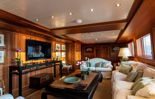 Large flat screen TV on superyacht 'Bleu De Nimes' with comfortable cream sofa and wooden table facing it
