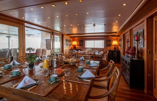 Wooden dining table fully laid out on superyacht 'Bleu De Nimes' with glass sliding doors behind