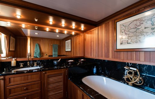 Marble sink and mirror with wooden panelling behind on superyacht 'Bleu De Nimes'