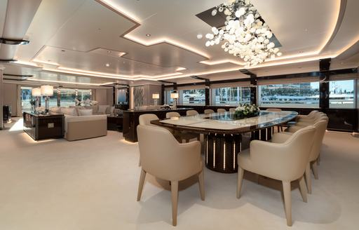 Large salon on superyacht O'PARI, showing open plan room with table and chairs in foreground and sofa and table in background