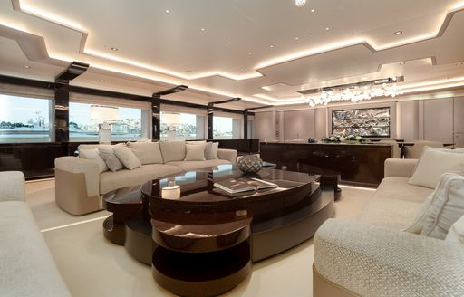 Two cream sofas on superyacht O'PARI with large wooden table in between them