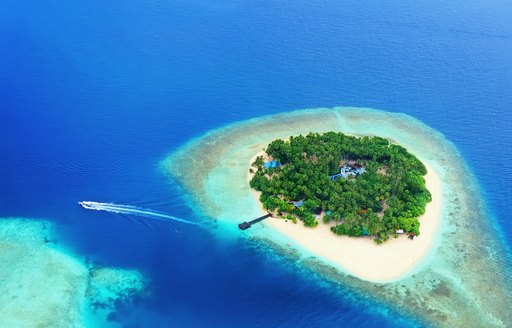 View of Maldives island from above with boat moving away from it