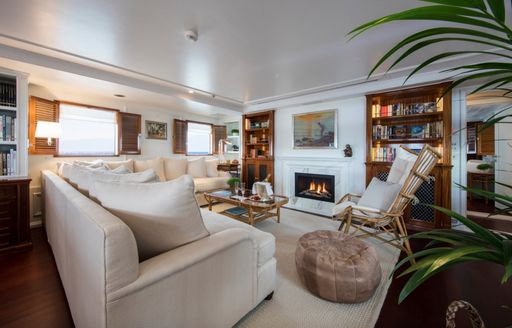 salon with fireplace and bookshelves on board charter yacht Haida 1929