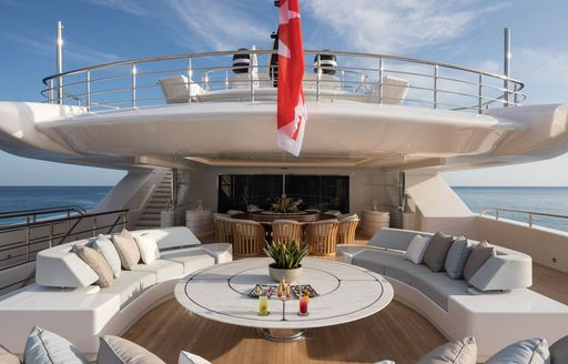 Comfortable seating and table on aft deck of superyacht O'PARI