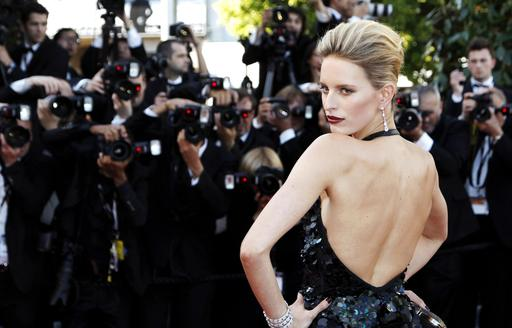 photographers take shots of a model walking the red carpet at the Cannes Film Festival