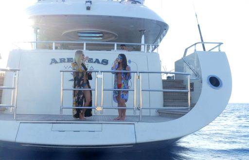 Swim platform of superyacht ARESTEAS, with charter guests enjoying a drink on board