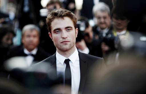 Robert Pattinson poses for photographs on the red carpet at the Cannes Film Festival