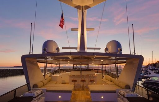 flybridge with bar and sun pads on motor yacht blackwood at sunset