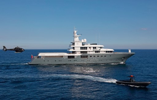 Planet Nine superyacht that features in Tenet on the sea with helicopter following behind and tender boat to the side