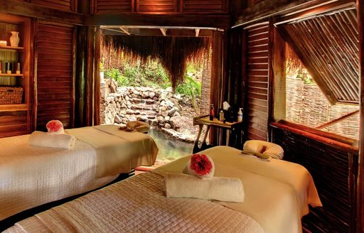 Two cream beds laid out besides a minature rocky waterfall in a Caribbean spa