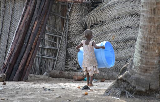child carries bucket on bwejuu island in tanzania