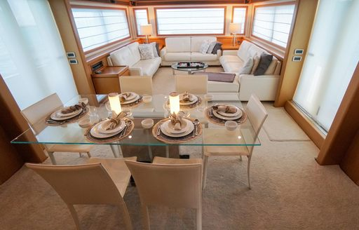 Light colored interiors of charter yacht NOMADA, with dining table in foreground and sofas in background