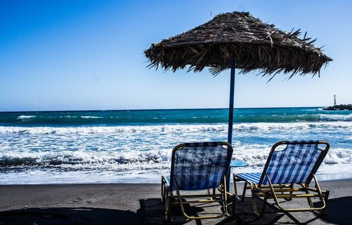 two deck chairs and a parasol on a black sand beach in Santorini, Greece