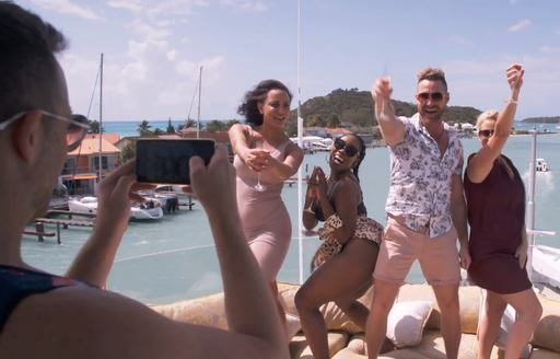 Person taking photo of four guests partying on boat