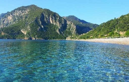 crystal clear waters and pine-covered mountains backing Cirali Beach in Turkey