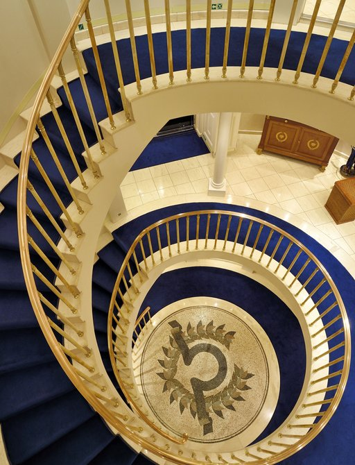 Blue and gold staircase in atrium of superyacht Christina O