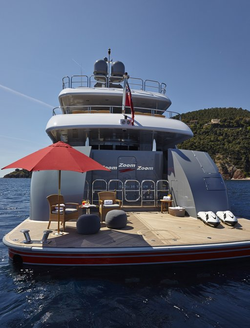 Beach club platform with chairs and parasol on board luxury yacht Zoom Zoom Zoom