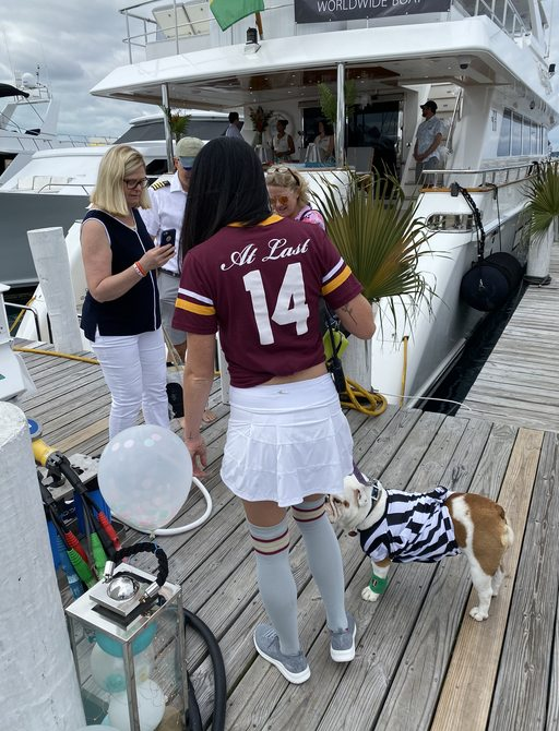 crew of luxury yacht at last with dog georgia on the docks