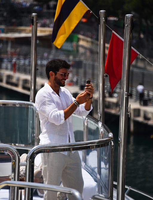 Man on deck of luxury yacht at Monaco Grand Prix taking pictures of cars going past
