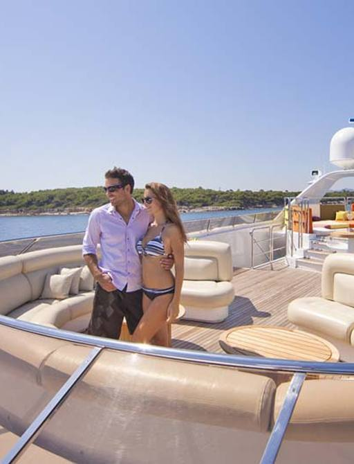 guests relax on the sundeck seating area of luxury yacht daloli