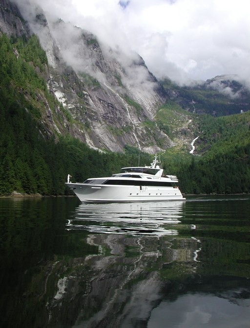Superyacht blackwood on the water in alaska with mountains and green forest backdrop