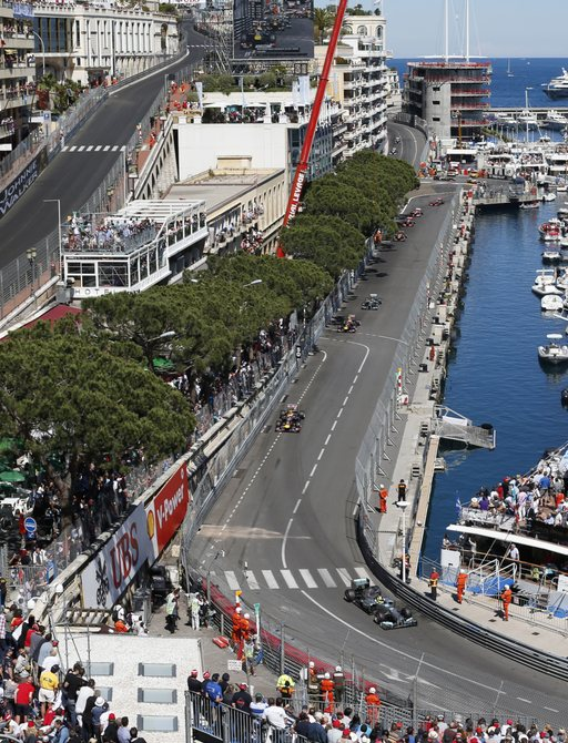 Superyachts at Port Hercules harbour, lined up along the track at Monaco Grand Prix as the cars race around the circuit